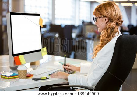 Side view of businesswoman using graphics tablet at desk in office