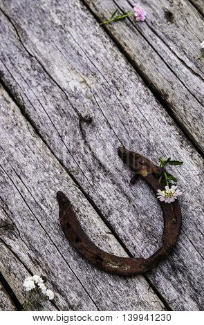 Old horseshoe on rough shabby wooden boards