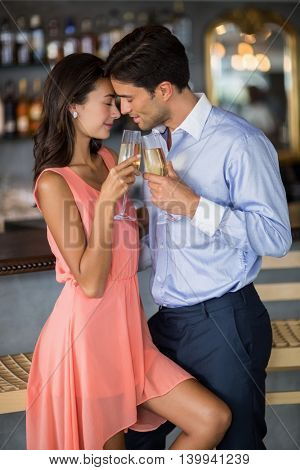 Young couple embracing while toasting a glasses of champagne