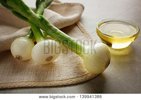 New onion with oil on grey background