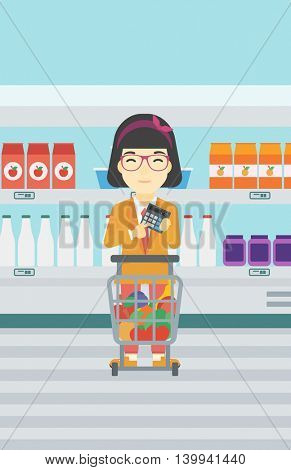 An asian young woman at the supermarket with calculator and supermarket trolley full with products. Woman checking prices with calculator. Vector flat design illustration. Vertical layout.