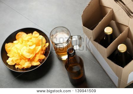 Paper beer package with mug and chips on grey background