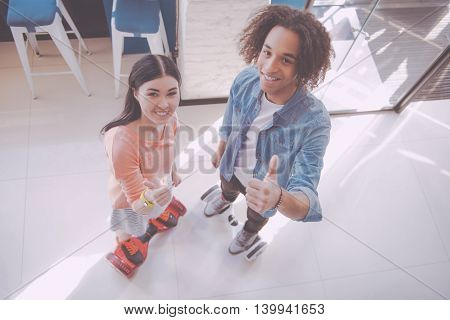 Good. Happy and cheerful young people riding hoverboards while being indoors in a cafe, posing and showing thumbs up