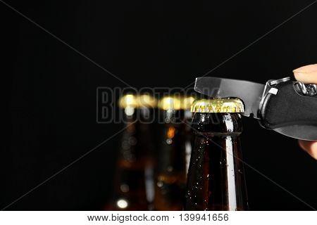 Female hand opening beer bottle on dark background