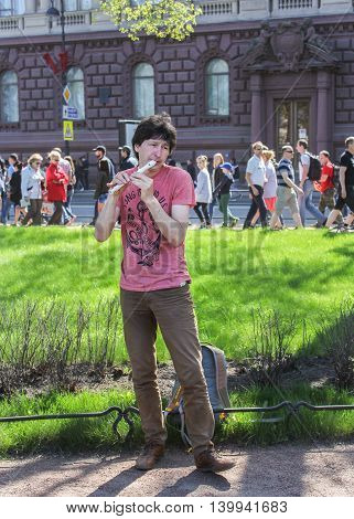 St. Petersburg, Russia - 9 May, Street performers playing the flute, 9 May, 2016. Vacationers people on the lawns and gardens in the city.
