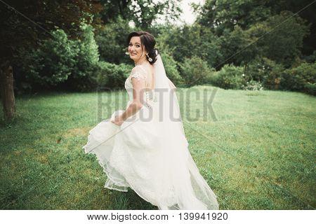 Beautiful wedding bride running in the garden.