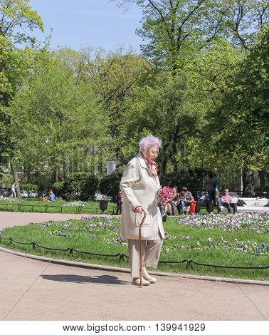 St. Petersburg, Russia - 9 May, An elderly woman with flowers, 9 May, 2016. Vacationers people on the lawns and gardens in the city.