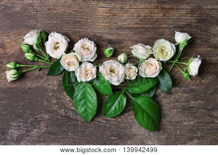 Assorted roses heads on wooden background