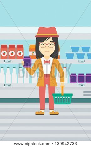 An asian woman holding shopping basket in one hand and milk product in the other. Female customer shopping at supermarket with basket. Vector flat design illustration. Vertical layout.