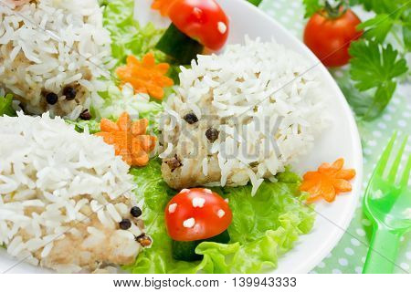 Baby healthy food: steamed hedgehogs meatballs with rice on vegetable garnish glade selective focus