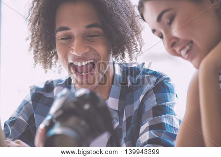 Funny. Cropped image of cheerful and delighted young people watching photos using their camera and having fun