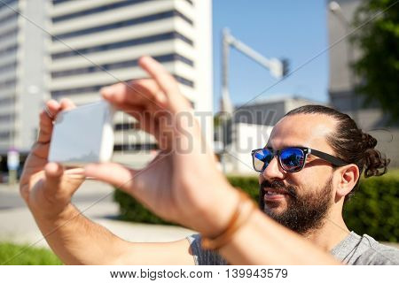 travel, tourism, technology and people concept - smiling man taking video or selfie by smartphone on summer city street