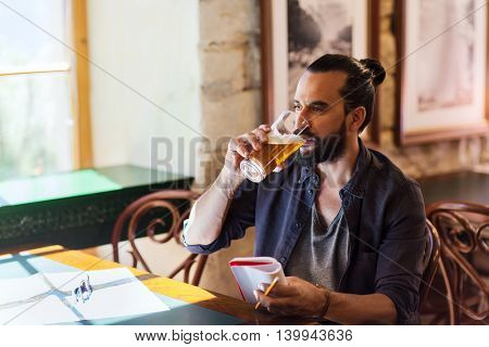 people, drinks, alcohol and leisure concept - happy young man with notebook drinking beer at bar or pub
