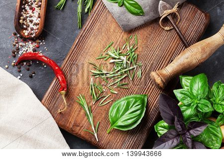 Herbs and spices cooking on stone table. Basil, rosemary, pepper and salt. Top view