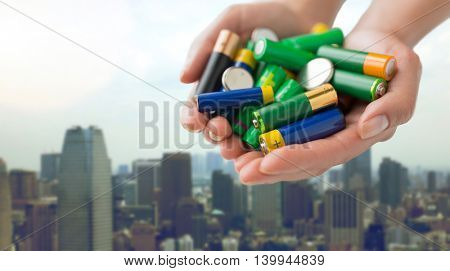 recycling, energy, power, environment and ecology concept - close up of hands holding alkaline batteries heap over singapore city skyscrapers background