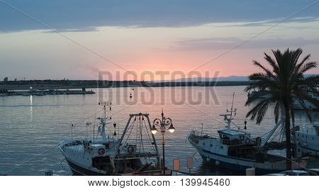 Colourful sunset view of a beach with reflexes in the harbor Molfetta. Italy