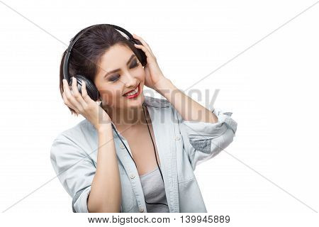 Music. Woman with big earphones headphones listening to music on mp3 player. Playful happy smiling young mixed race Asian Caucasian woman isolated on white background.