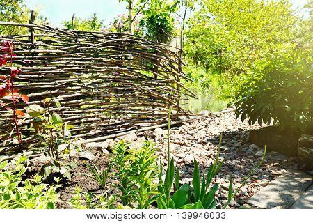 Wicker wooden fence in garden