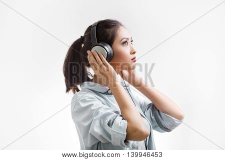 Music. Woman with big earphones headphones listening to music on mp3 player. Young mixed race Asian Caucasian woman isolated on white background.