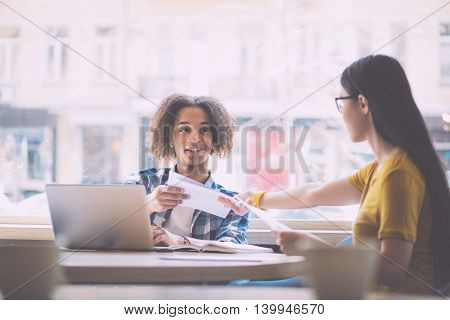 Friendly air. Cheerful young woman giving some papers her male colleague while sitting at the table and working