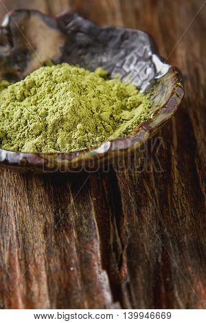Dry Matcha Tea In A Small Brown Plate. Dark Wood Background