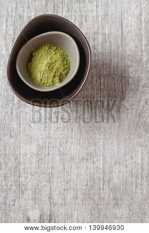 Dry Matcha Tea In A Small Brown Plate. Grey Wood Background. Top