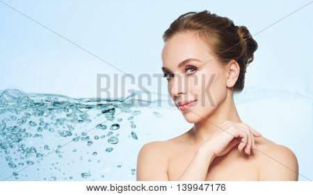 health, people, plastic surgery and beauty concept - beautiful young woman face over water splash bubbles on blue background