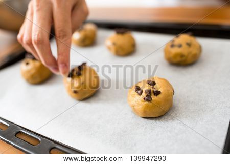 Woman putting paste on baking tray