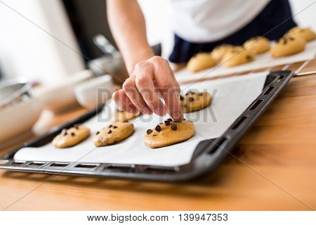 Woman adding chocolate bean on cookies