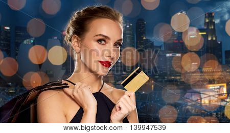 people, luxury and sale concept - beautiful woman with credit card and shopping bags over night singapore city and lights background