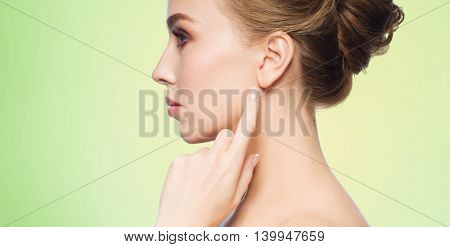 health, people and beauty concept - beautiful young woman pointing finger to her ear over green natural background