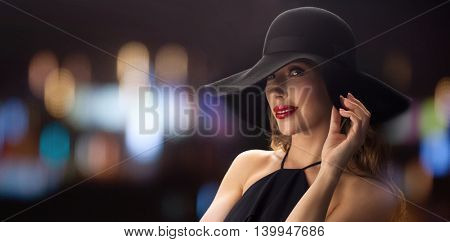people, luxury and fashion concept - beautiful woman in black hat over blurred night lights background
