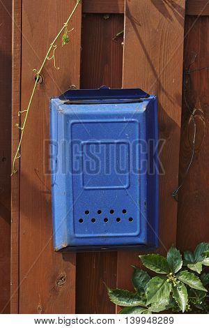 blue postbox mail box on red lumber wall
