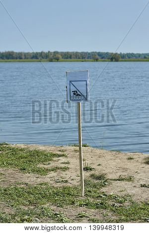 warning board no swimming on lake bank