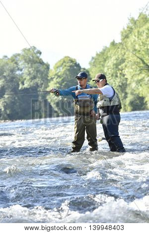 Flyfisherman with fishing guide in river