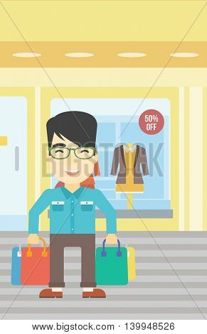 An asian man holding shopping bags on the background of boutique window with dressed mannequins. Happy young man carrying shopping bags. Vector flat design illustration. Vertical layout.