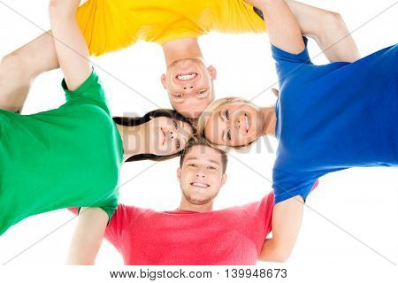 Happy students in colorful clothing standing together hugging.