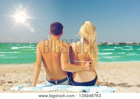 picture of couple sitting on the beach