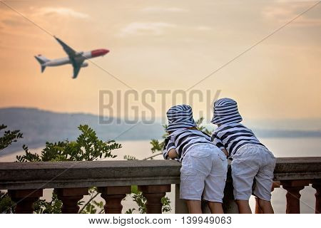 Two Little Children, Boy Brothers, Looking At Landing Airplane In The Sky Over The Sea