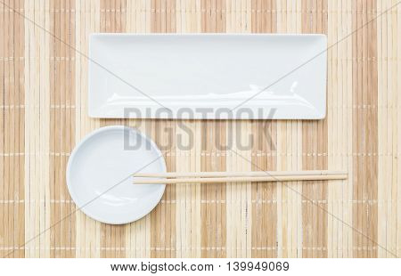 Closeup white ceramic square dish and chalice with wood chopsticks on wood mat textured background on dining table in top view
