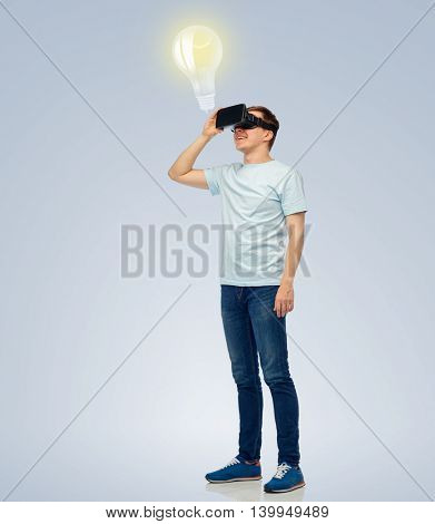 3d technology, virtual reality, entertainment, cyberspace and people concept - happy young man with virtual reality headset or 3d glasses looking at light bulb projection