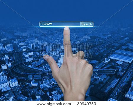 Hand pressing search www button over street expressway and city tower Searching system and internet concept