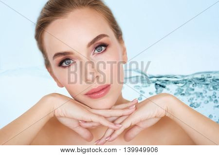 beauty, people and body care concept -beautiful young woman face and hands over water splash bubbles on blue background