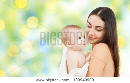 family, motherhood, parenting, people and child care concept - happy mother holding adorable baby over green holidays lights background