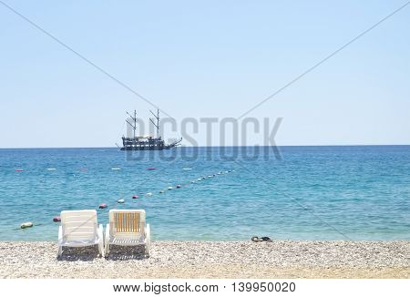 Romantic view of the beach. Two beach chairs against blue sky azure water yellow sand and old sea ship on a horizon. Vacation background. Pair of lounge chairs. Beach relax coastline view.