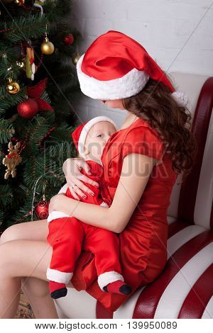 Mother breast feeding baby. Family dressed in Santa`s costumes. Winter holidays. Christmas new year and people concept.
