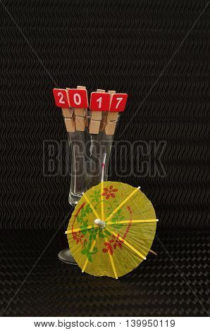 2017 spelled with red blocks displayed on the rim of a shooter glass with a yellow  cocktail umbrella on a black background