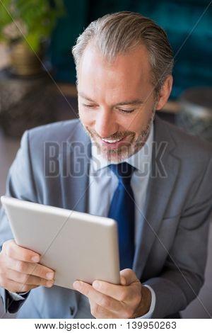 Happy businessman using digital tablet in café
