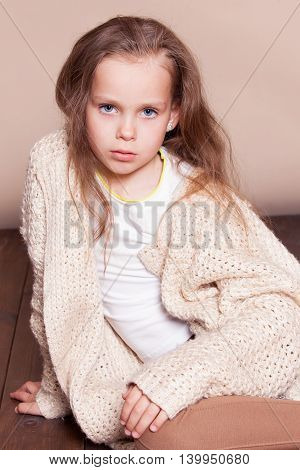 little girl sitting on the floor and sad