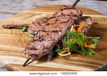 Grilled kebab skewer served on a wooden board